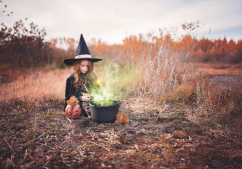 girl in witches costume with pumpkin and cauldron