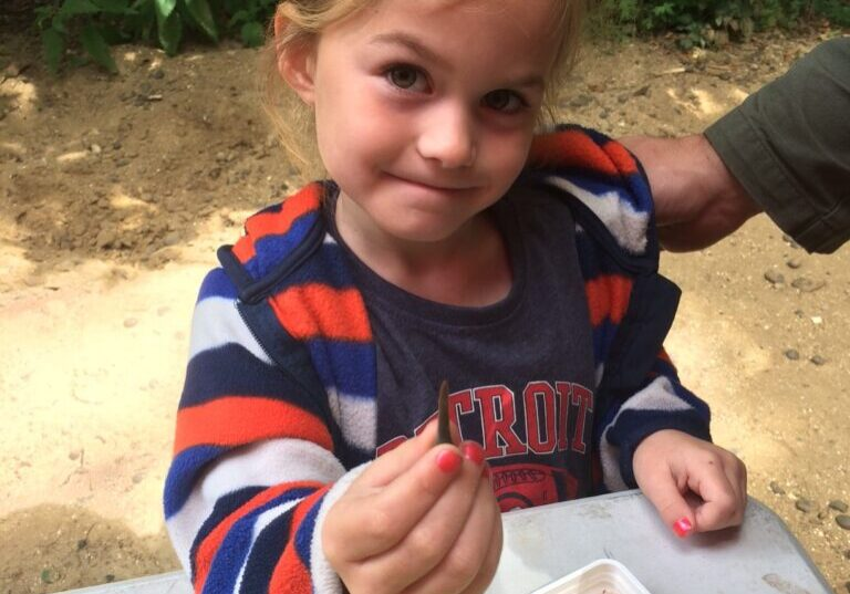 Girl holding a shark's tooth fossil