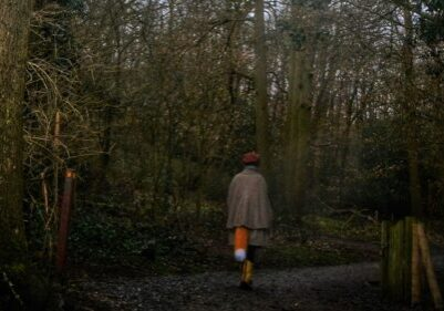 Lady wearing a fox tail walking through the woods