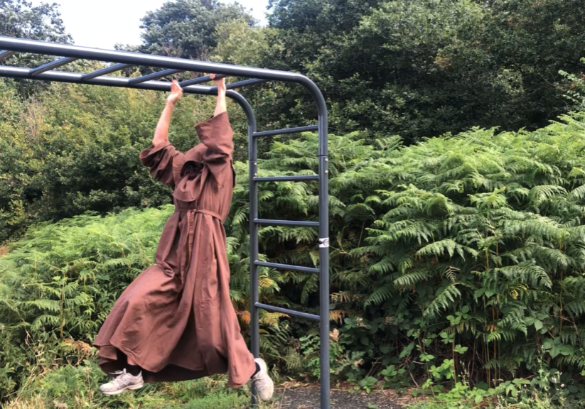 A man dressed as a monk using the trim trail