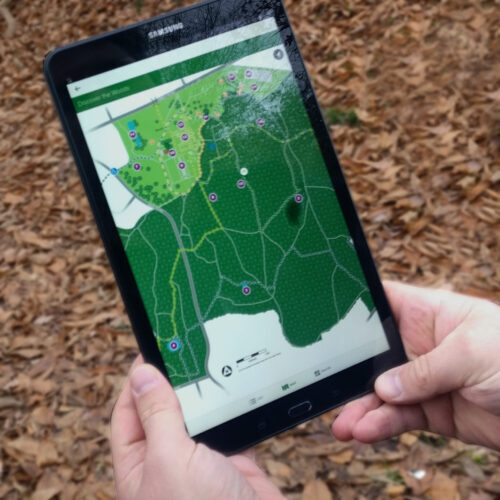 Person holding tablet with map showing on screen